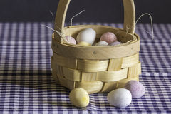 Chocolate Eggs in Small Basket. A simple display of chocolate eggs in a small basket on a checkered background Stock Image
