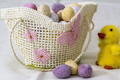 Chocolate Eggs in small basket. A small white basket with Chocolate Eggs and a Toy Chick to the side Stock Photography