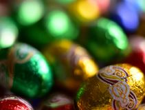 Chocolate eggs wrapped in shiny colored paper. Chocolate eggs wrapped in shiny golden, green, blue and red paper. Focus is on the egg on the right, the other Royalty Free Stock Image