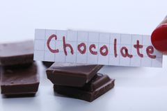Chocolate, English word on a white note, pieces of chocolate on background. Learn new language, English word for Chocolate written on a note near some chocolate Stock Image
