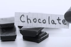 Chocolate, English word on a white note, pieces of chocolate on background. Learn new language, English word for Chocolate written on a note near some chocolate Stock Images