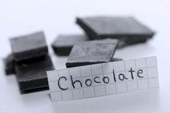 Chocolate, English word on a white note, pieces of chocolate on background. Learn new language, English word for Chocolate written on a note near some chocolate Royalty Free Stock Photo