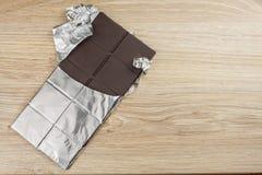 Chocolate envuelto en papel de aluminio en un tablero de madera Imagen de archivo