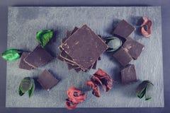 Chocolate escuro na pedra colorida com as folhas do vermelho e do verde Fotos de Stock