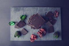 Chocolate escuro na pedra colorida com as folhas do vermelho e do verde Fotografia de Stock Royalty Free