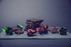 Chocolate escuro na pedra colorida com as folhas do vermelho e do verde Imagens de Stock Royalty Free