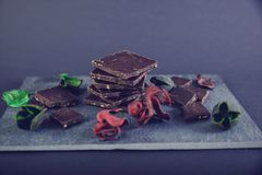 Chocolate escuro na pedra colorida com as folhas do vermelho e do verde Fotos de Stock Royalty Free