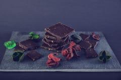 Chocolate escuro na pedra colorida com as folhas do vermelho e do verde Foto de Stock