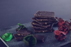 Chocolate escuro na pedra colorida com as folhas do vermelho e do verde Imagem de Stock Royalty Free