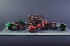 Chocolate escuro na pedra colorida com as folhas do vermelho e do verde Imagem de Stock