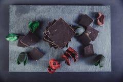 Chocolate escuro na pedra colorida com as folhas do vermelho e do verde Foto de Stock Royalty Free