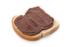 Chocolate espalhado em uma fatia de pão Imagem de Stock Royalty Free