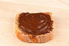 Chocolate espalhado na fatia de pão Imagem de Stock Royalty Free