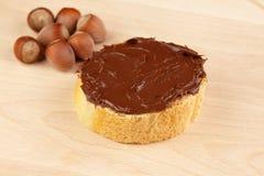 Chocolate espalhado na fatia de pão Fotografia de Stock
