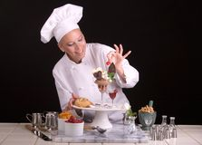 Chocolate extreme dessert. Front view of a passive posed female Pastry Chef finalizing an elegant chocolate dessert plate Stock Photography