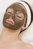 Chocolate Face Mask. A beautiful young brunette woman rests after having a chocolate face mask applied by a beautician Stock Image