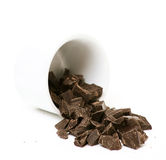 Chocolate falling from white dish Royalty Free Stock Photography