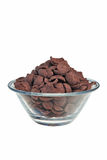 Chocolate flakes. Chocolate flakes in transparent bowl over white background Stock Photos