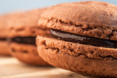 Chocolate flavor Macaroon placed on wood and leather Royalty Free Stock Photography