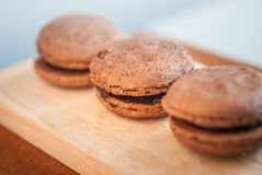 Chocolate flavor Macaroon placed on wood and leather Stock Image