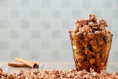 Chocolate flavored popcorn in the yellow glass and on the brown wood table with cinnamon background stock images