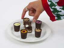 Chocolate with flavors. Flavored chocolates with a hand picking one of Royalty Free Stock Photography