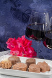 Chocolate flowers red wine glasses Stock Image