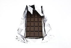 Chocolate on a foil. On a white background is isolated Stock Photos