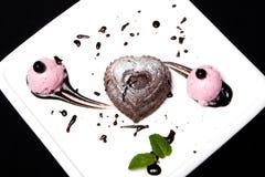 Chocolate fondan del postre con helado en una placa blanca en un fondo negro Postre franc?s exquisito del chocolate fondan fotos de archivo libres de regalías