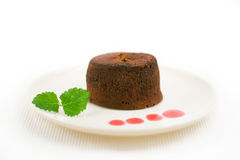 Chocolate fondant. With peppermint leaves and drops of strawberry sauce royalty free stock image
