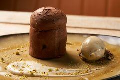 Chocolate Fondant cake and pistachio ice cream with English cream. Pistachio crumble and sauce bailies. Exclusive restaurant dessert food served on a table stock images