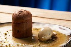 Chocolate Fondant cake and pistachio ice cream with English cream. Pistachio crumble and sauce bailies. Exclusive restaurant dessert food served on a table royalty free stock photos