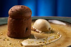 Chocolate Fondant cake and pistachio ice cream with English cream. Pistachio crumble and sauce bailies. Exclusive restaurant dessert food served on a table stock image