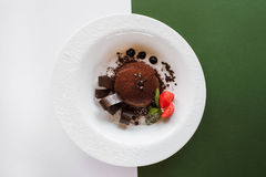 Chocolate fondant on contrast colorful background. Of white and green. Delicious dessert with decoration from strawberry and mint serving in restaurant, top Royalty Free Stock Images