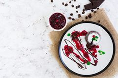 Chocolate fondant with cranberry sauce. Top view. Chocolate fondant with cranberry sauce royalty free stock photography