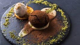 Chocolate fondant with creme anglaise and vanilla ice cream. Exquisite dessert on black background. Chocolate fondant, creme anglaise and vanilla ice cream royalty free stock image