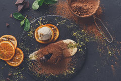 Chocolate fondant with creme anglaise and vanilla ice cream. Exquisite french dessert. Chocolate fondant with creme anglaise and vanilla ice cream on round slate stock photography