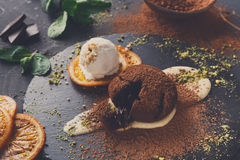Chocolate fondant with creme anglaise and vanilla ice cream. Exquisite french dessert. Chocolate fondant, creme anglaise and vanilla ice cream, sprinkled with royalty free stock image