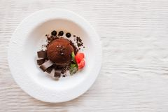 Chocolate fondant with decoration on wooden table. Chocolate fondant with decoration from strawberry and mint on wooden table. Delicious dessert serving in stock photos