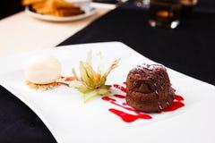Chocolate fondant with ice cream. Chocolate fondant with vanilla ice cream and raspberry sauce stock photo