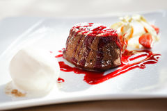 Chocolate fondant with ice cream. Chocolate fondant with vanilla ice cream and raspberry sauce stock photos