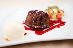 Chocolate fondant with ice cream. Chocolate fondant with vanilla ice cream and raspberry sauce royalty free stock photo