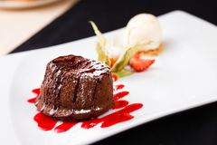 Chocolate fondant with ice cream. Chocolate fondant with vanilla ice cream and raspberry sauce royalty free stock photography