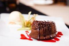 Chocolate fondant with ice cream. Chocolate fondant with vanilla ice cream and raspberry sauce royalty free stock images