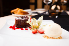 Chocolate fondant with ice cream. Chocolate fondant with vanilla ice cream and raspberry sauce stock images
