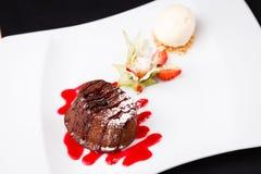 Chocolate fondant with ice cream. Chocolate fondant with vanilla ice cream and raspberry sauce stock image