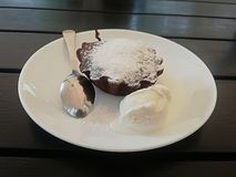Chocolate fondant with ice cream on a white plate on a wooden table. Background royalty free stock photography