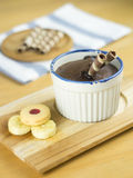 Chocolate fondant lava cake. With cookies and banana in ceramic cup on wooden tray royalty free stock photography
