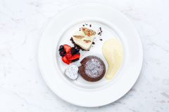 Chocolate fondant lava cake with ice cream strawberries and berries. On white plate on marble serface royalty free stock photography