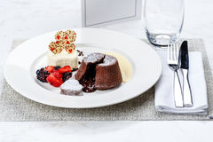 Chocolate fondant lava cake with ice cream strawberries and berries. On white plate on marble serface stock image